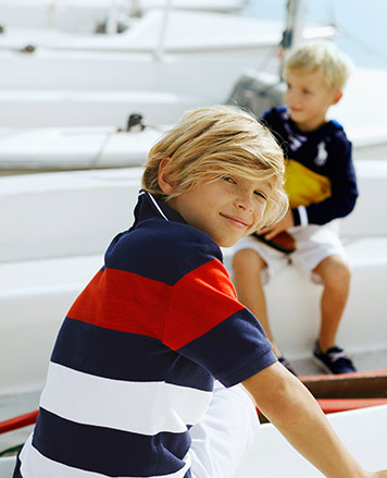 Boy wears red white and blue striped Polo shirt.