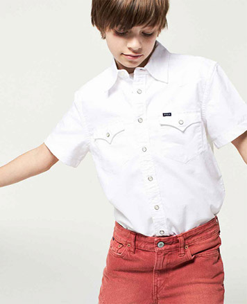 Boy wears white button-down shirt and red pants.
