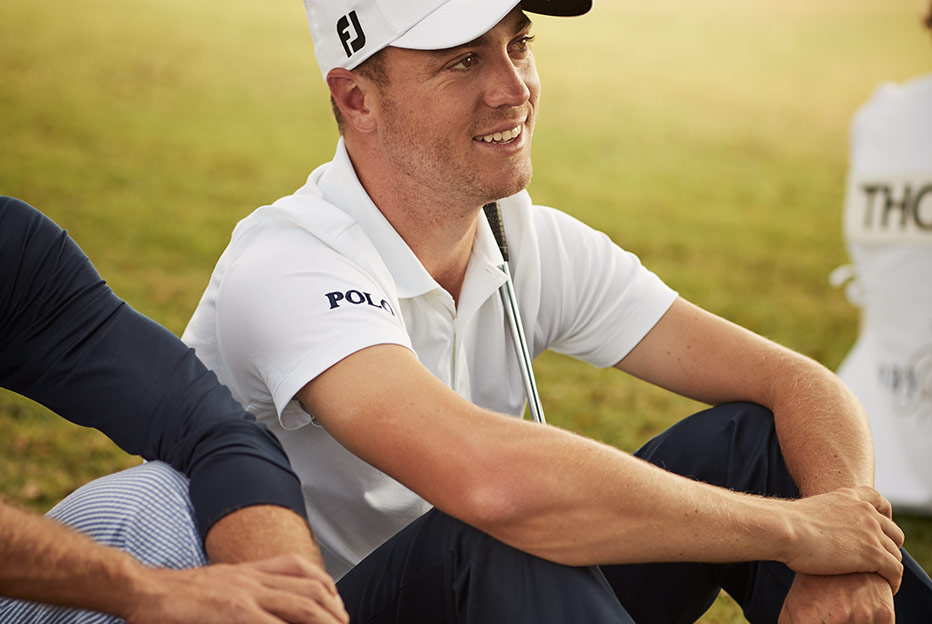 Justin Thomas sits on green in shirt with Polo text at sleeve