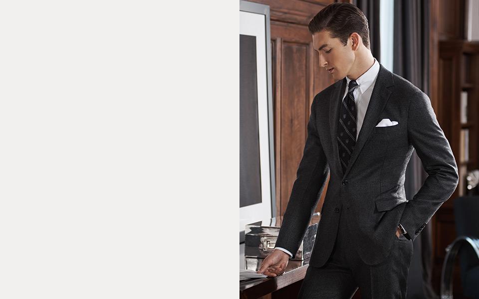 Man in black suit looks at newspaper