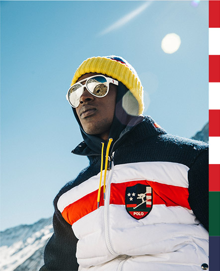 Man on mountain in hybrid jacket with ski graphics & patches