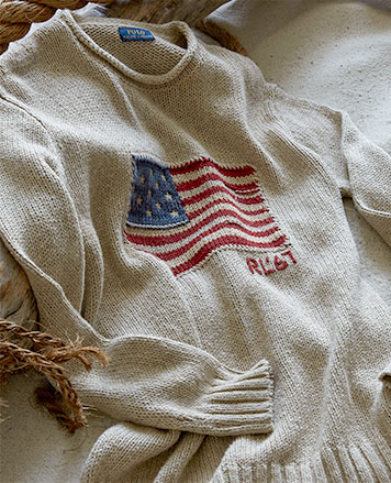 White rollneck sweater with American flag motif at chest