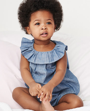 Baby girl wears chambray shortall with ruffled collar.
