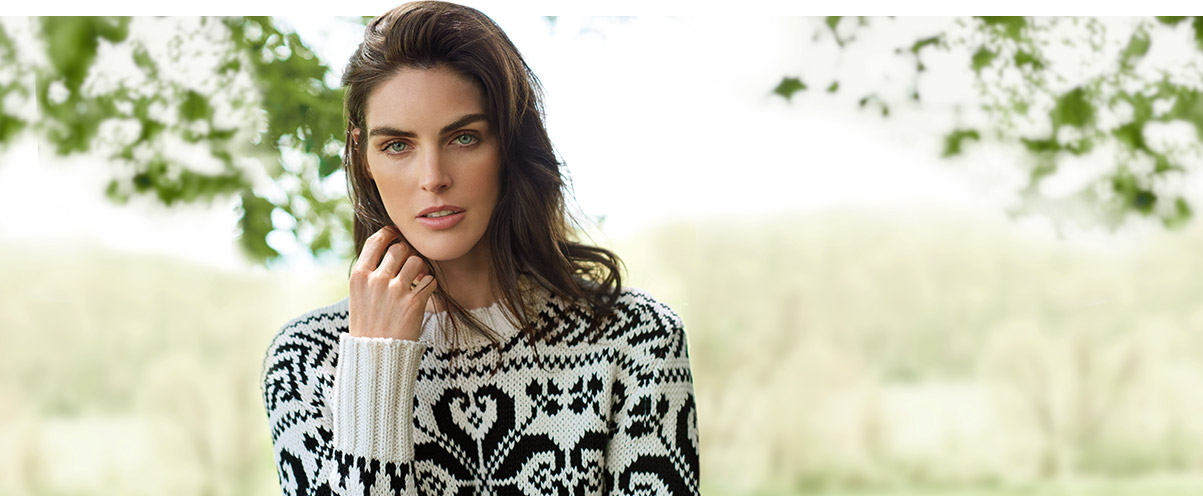 Woman wears black-and-white patterned crewneck sweater.