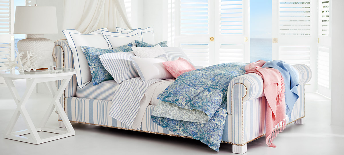 Upholstered sleigh bed with multiple pillows & blankets in blue & pink