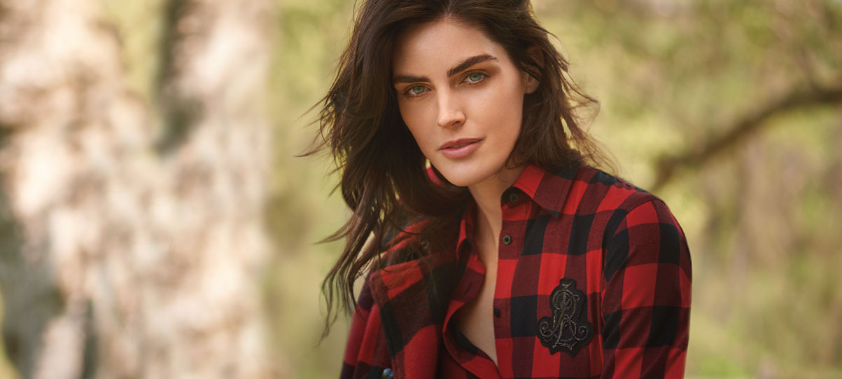 8aa78dae74f8 Woman wears red-and-black flannel button-down with embroidered crest. Lauren