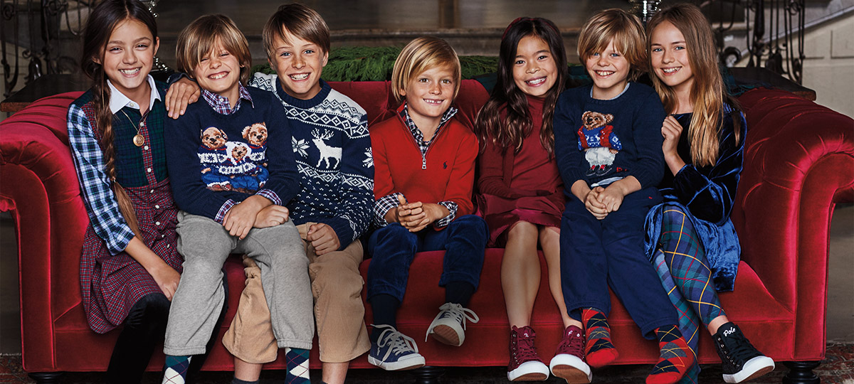 Kids on red velvet couch wear festive holiday outfits.