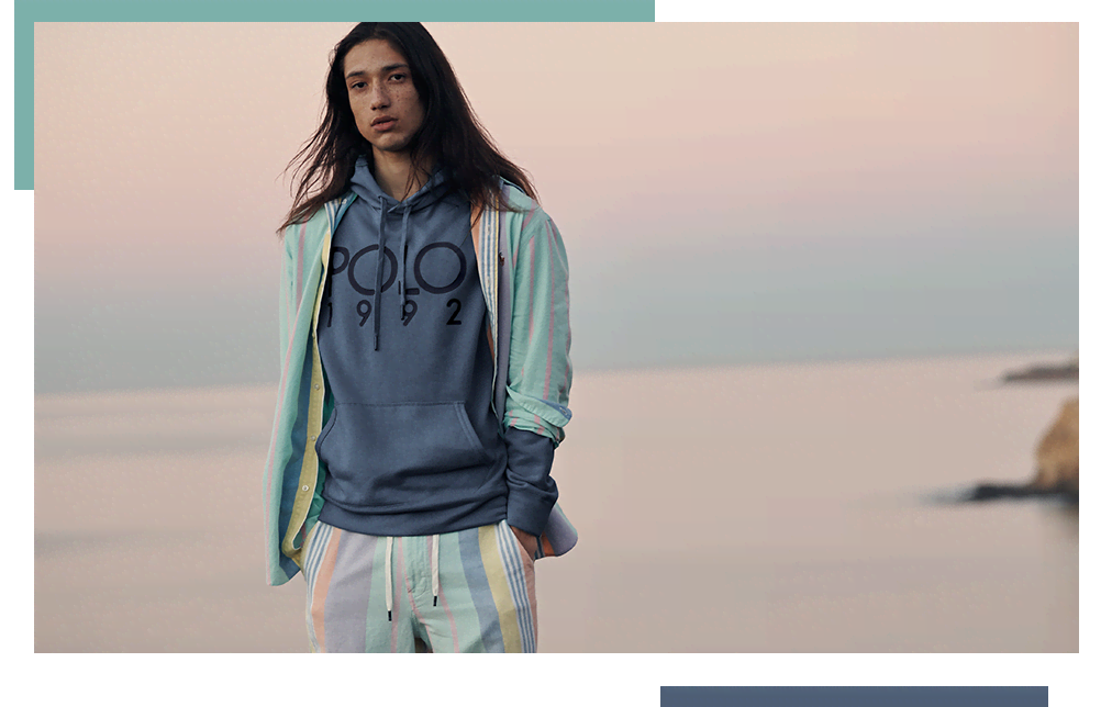 Model wears blue Polo hoodie and multicolored striped shorts.