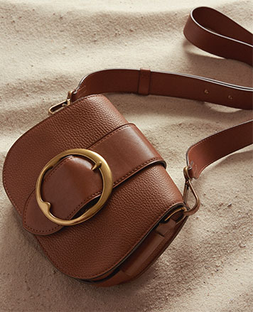 Pebbled brown leather shoulder bag with large buckle at front