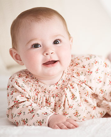 Baby girl wears light-pink floral dress.