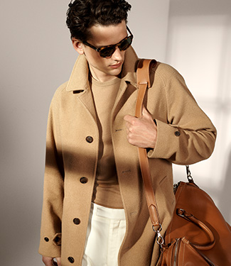 Man in tan coat & sunglasses carrying shoulder bag