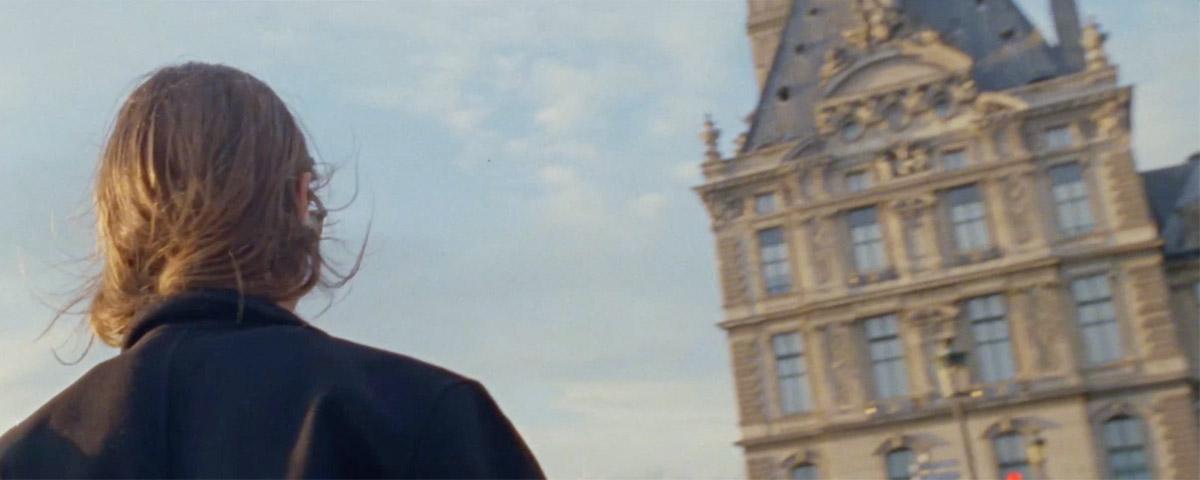 Woman in town wearing sunglasses & overcoat