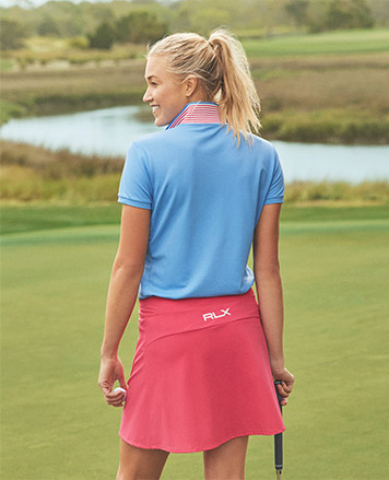 Woman on green in coral RLX skort & light blue Polo