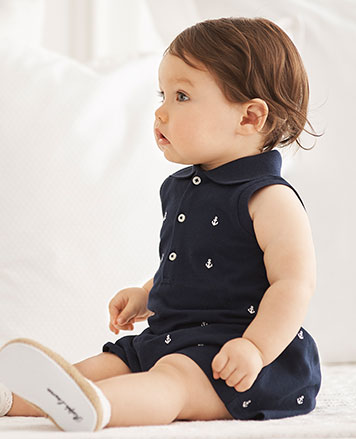 Baby girl wears navy romper with allover embroidered anchors.