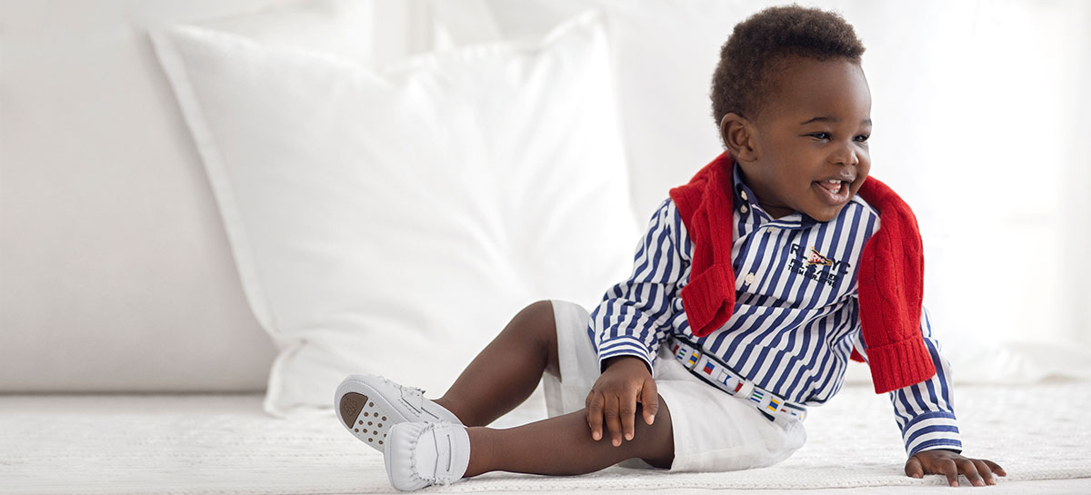 Baby boy wears blue-and-white striped button-down, white shorts, and embroidered belt.