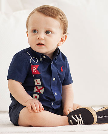 Navy shortall with embroidered flags and rope at the side