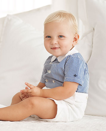 Baby boy wears blue-and-white striped shirt with attached white shorts.