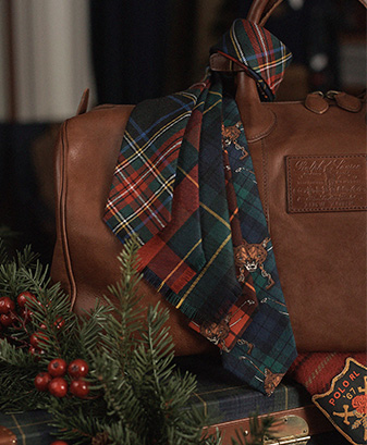 Plaid ties draped over brown leather duffel bag
