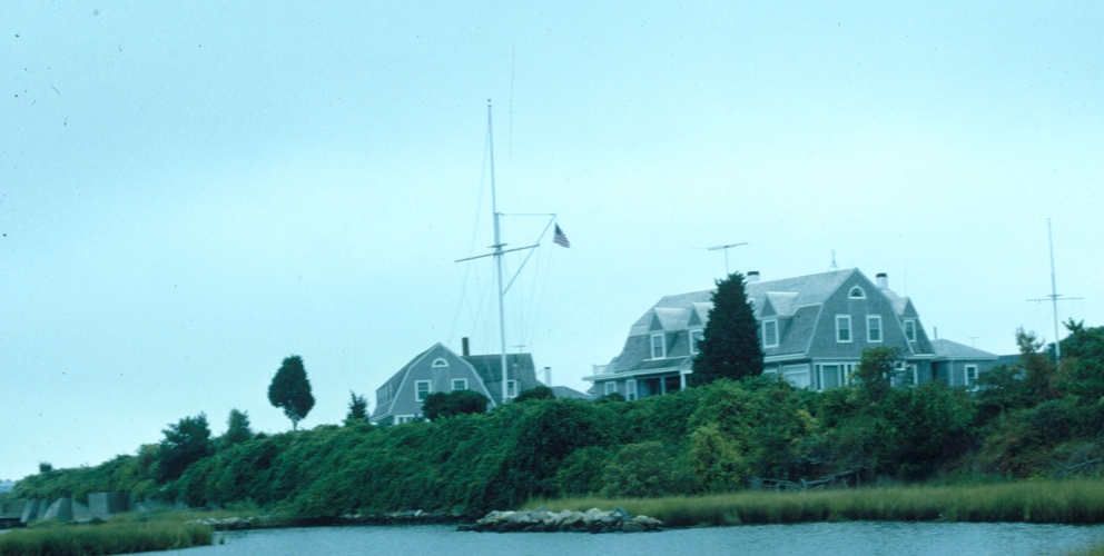 Grey paneled cottages by grassy inlet