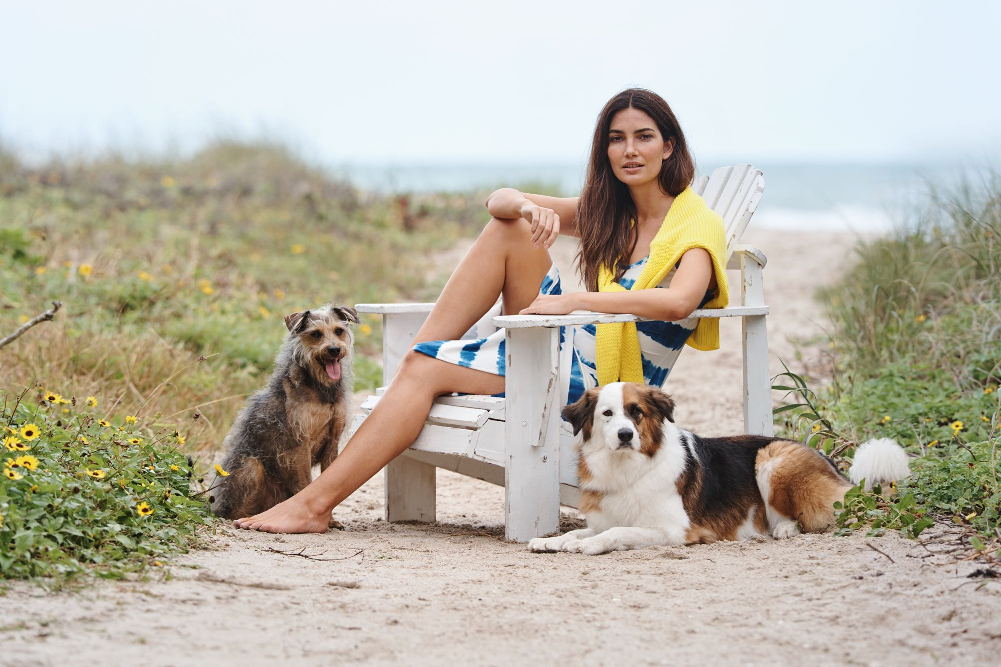 Woman in tie-dye dress sits on chair on beach with dogs.
