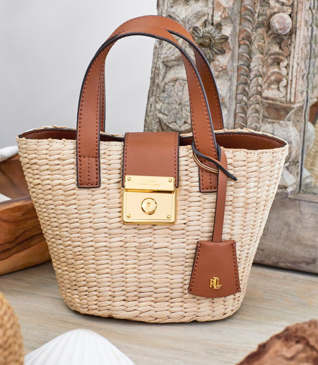 Woven straw bag with brown leather handles.
