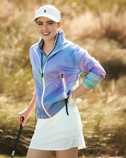 Woman in white golf skirt & light purple jacket