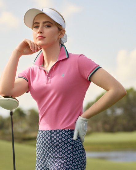 Woman in pink golf Polo shirt on golf course