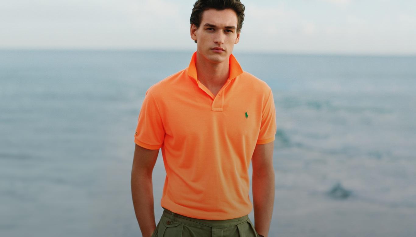 Man wears orange Earth Polo shirt and green pants.