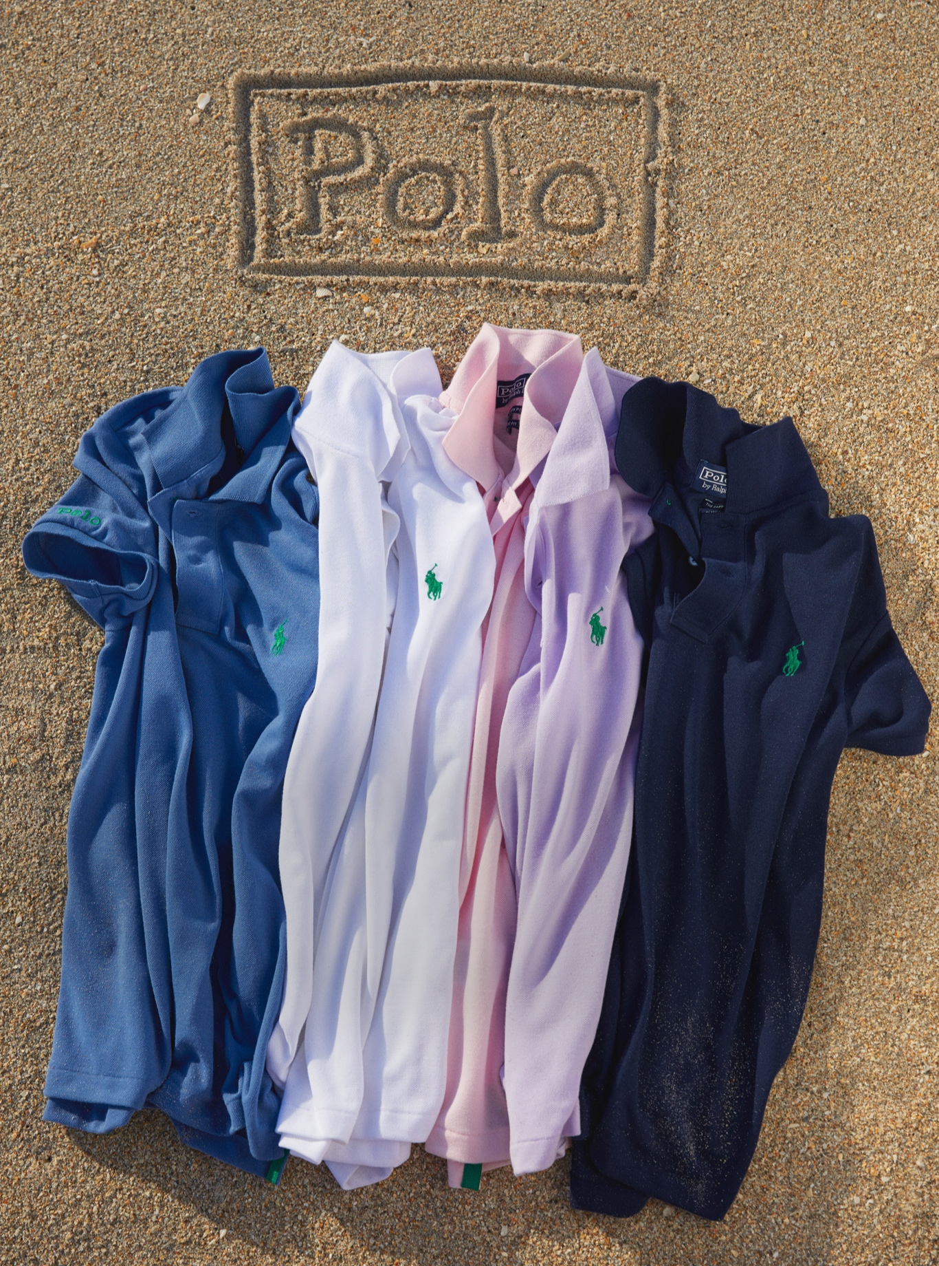 Earth Polo shirts in various colors on sandy beach.