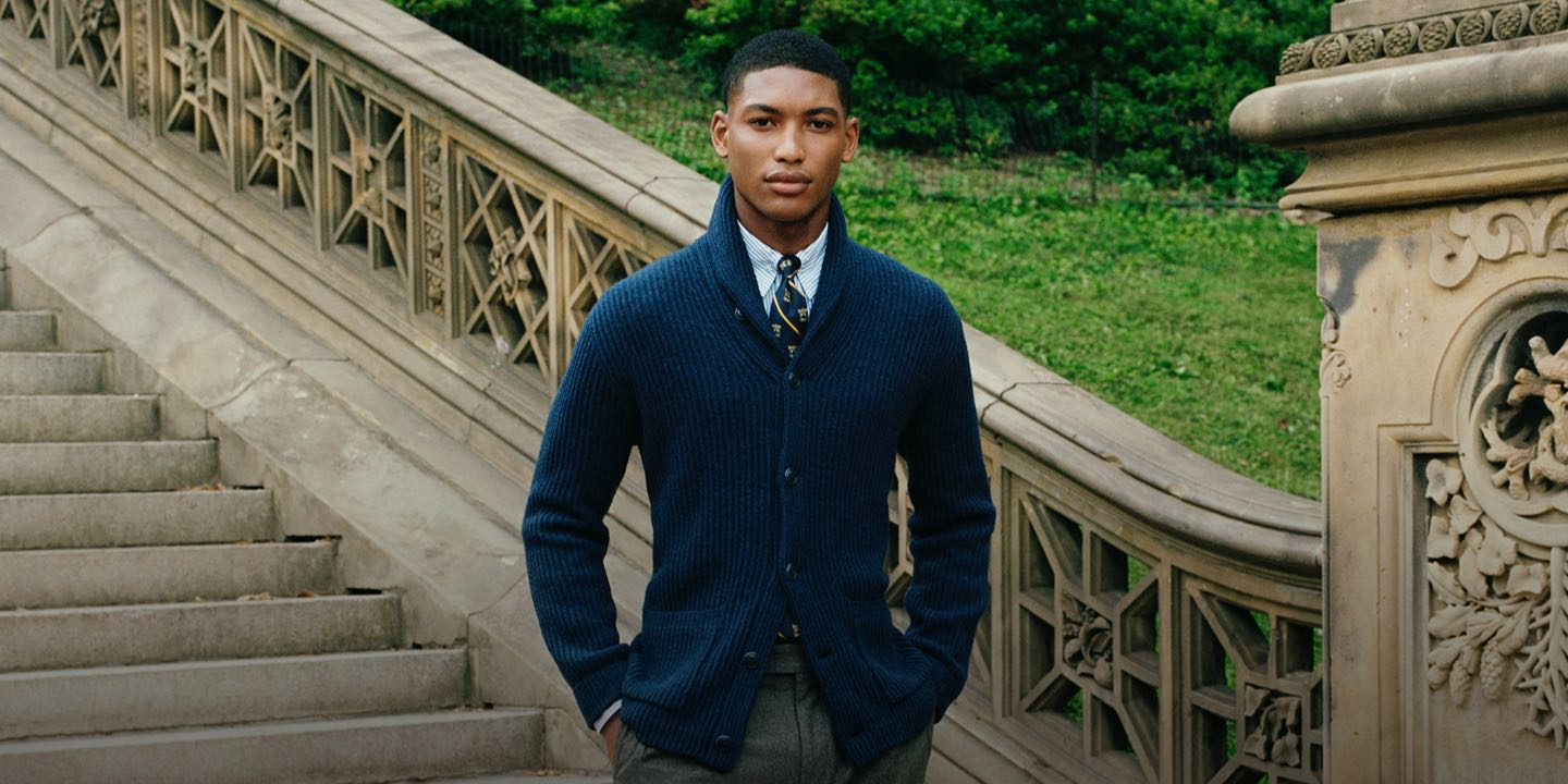 Man wears navy cardigan and tie on stone staircase.