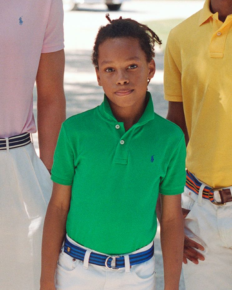 Boy wears green Polo shirt and white jeans.