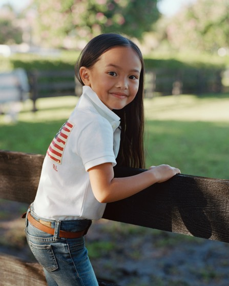 Girl wears white Polo with flag motif at back & jeans