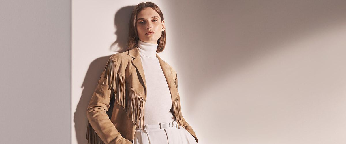 Woman in tan fringe jacket & off-white turtleneck & trousers