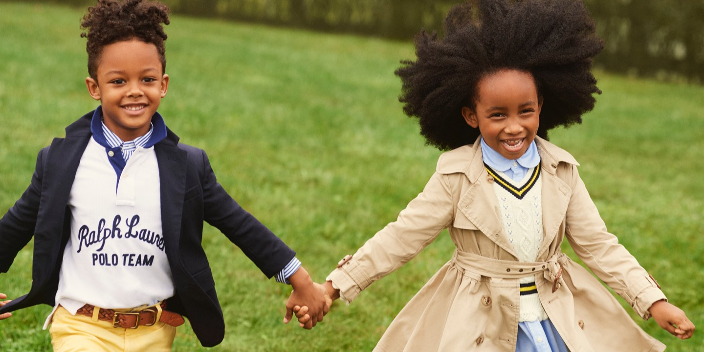Boy in navy blazer holding hands with girl in tan trench coat