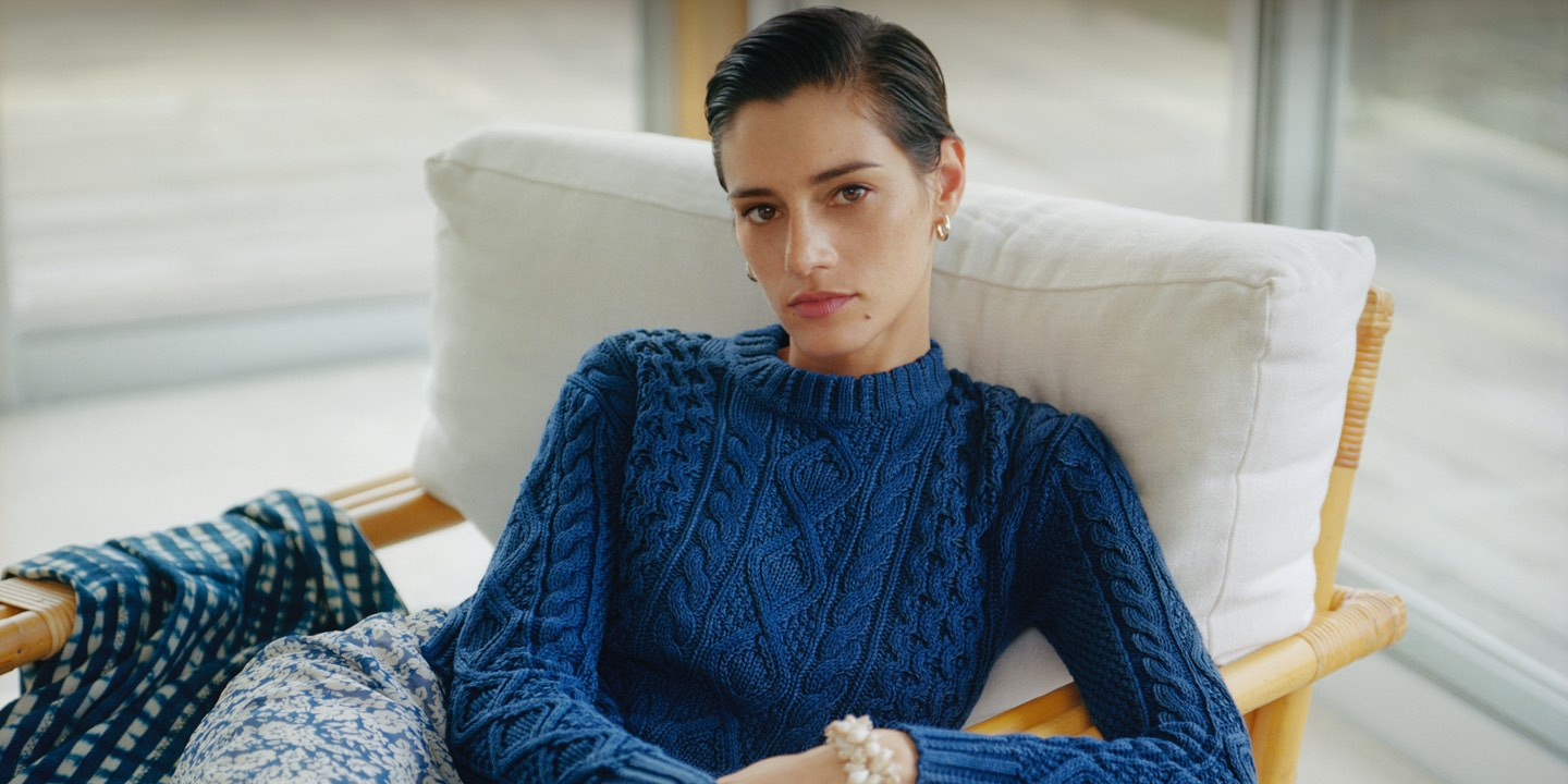 Woman in multi-stitched blue sweater