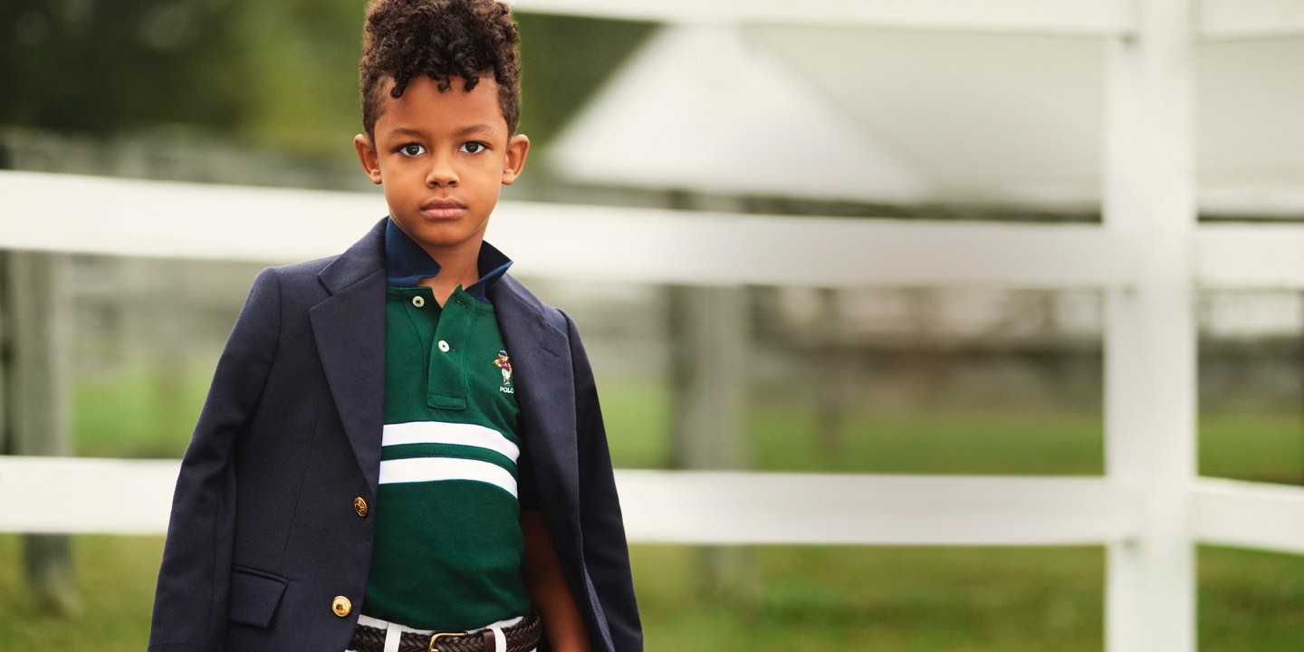 Boy in striped green Polo with navy blazer over shoulders
