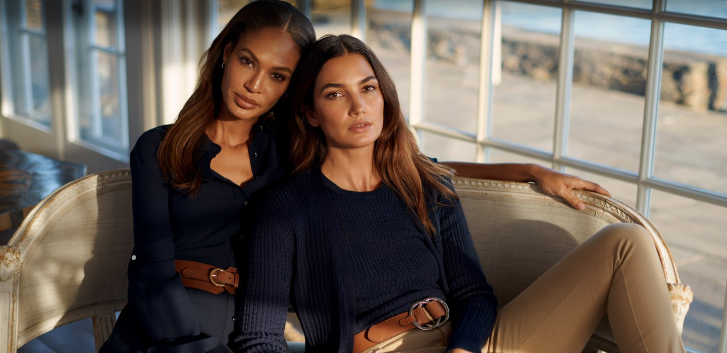 Joan Smalls and Lily Aldridge in navy outfits on chair.