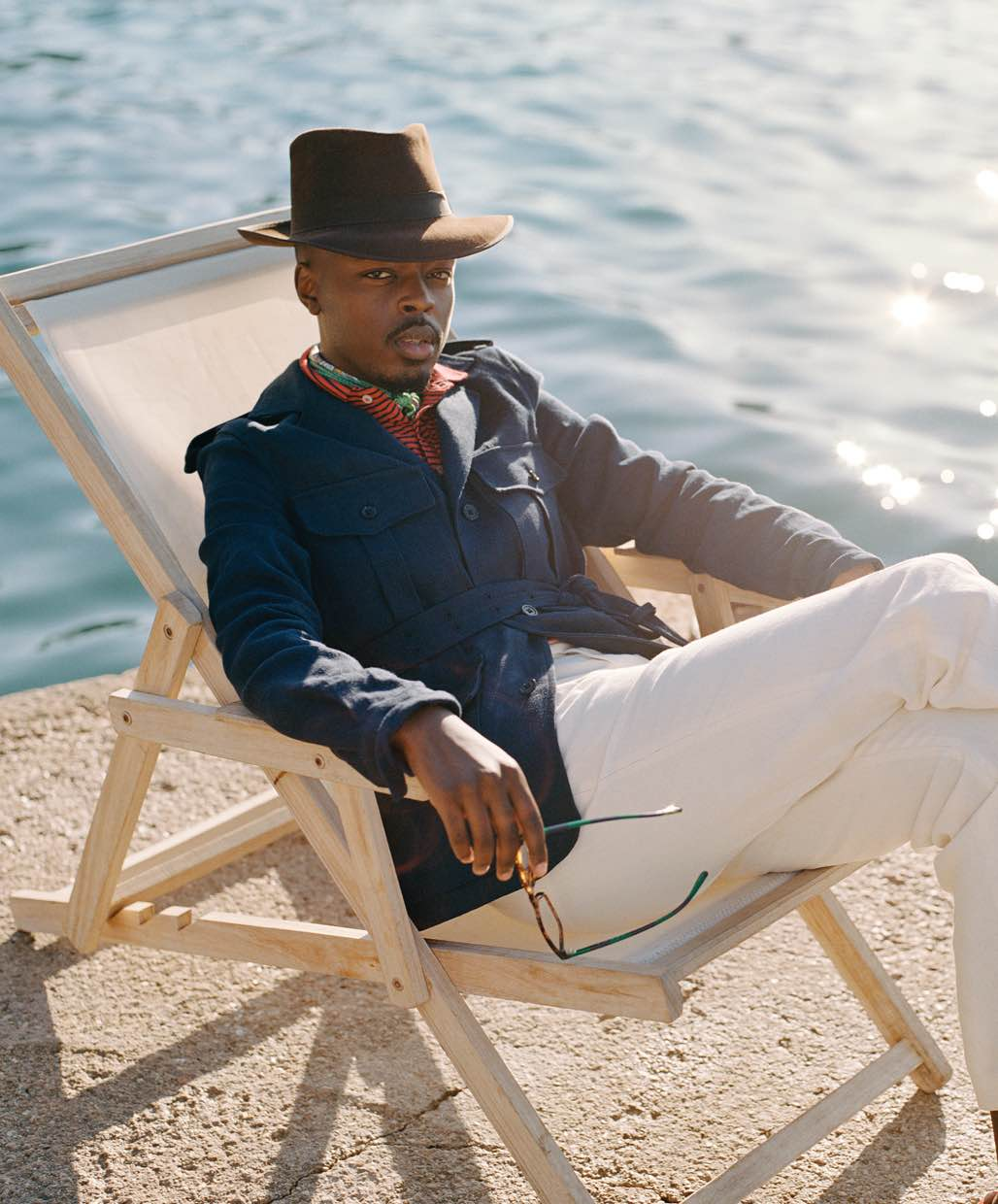 Man on beach chair wears navy jacket and white pants.