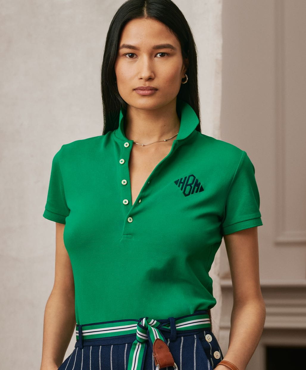 Woman in green Polo shirt with navy embroidered monogram