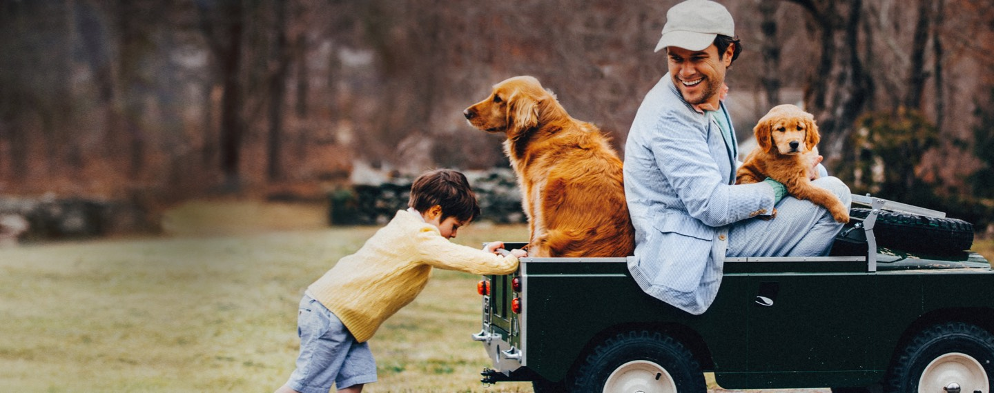Son in cable sweater pushing Dad in sport coat in toy jeep