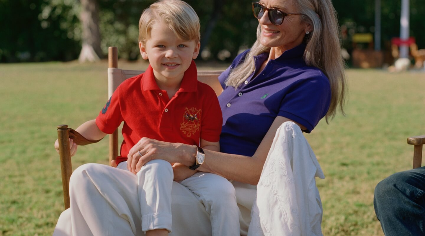 Boy in red Polo shirt sits on woman's lap.
