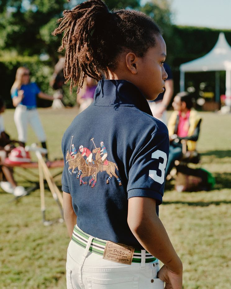 Boy wears navy Polo with equestrian graphic at back.