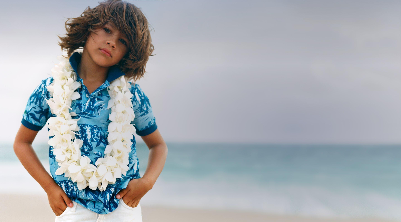Boy in blue Hawaiian-print Polo shirt by ocean