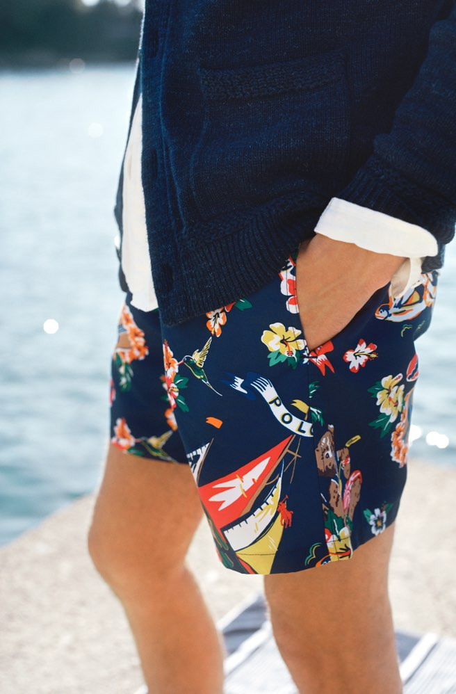 Man in navy swim trunks with colorful floral & sailboat motifs