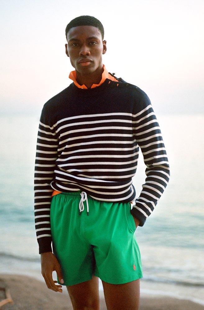 Man wears green drawstring swim trunks & striped sweater