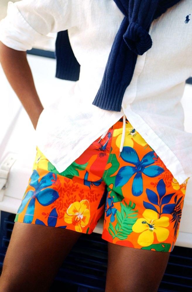 Man wears colorful Hawaiian-print swim trunks