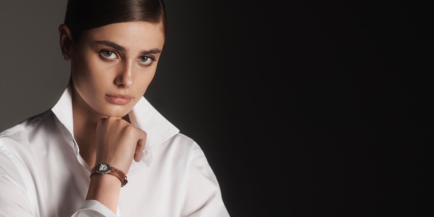 Woman wears watch with stirrup-shaped dial & brown leather strap