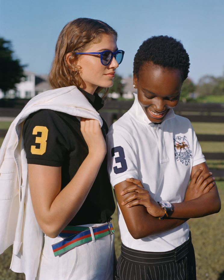 Women wear black & white Polo shirts with 3 at the sleeve.