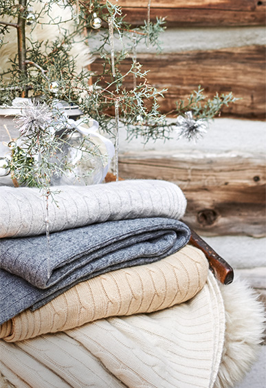 Stack of cable-knit throw blankets in muted winter hues