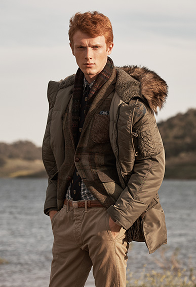 Man standing outside by a lake wearing a brown puffer coat with faux fur collar